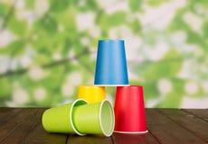 Uppsättning av mångfärgade plast-koppar på trätabellen Royaltyfri Fotografi