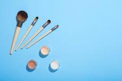 Uppsättning av makeupborstar och mineraliska ögonskuggor på blå bakgrund Royaltyfri Foto