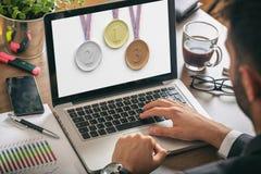 Uppsättning av medaljer på en bärbar datorskärm - man på arbete arkivfoton