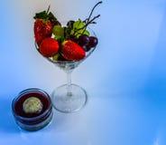 Uppsättning av ny frukt i ett exponeringsglas och en söt jordgubbeefterrätt på Royaltyfri Foto
