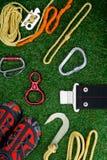 Uppsättning av objekt på den gröna gräsmattan, att lyfta bergen, rep, carabiners av olika modeller, skor och säkerhetsbältet arkivfoto