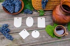 Uppsättning av olika etiketter som är lekmanna- bredvid korg, bunken med druvor, kruset och koppen med vin på lantligt trä Vindan Arkivfoto