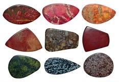 Uppsättning av olika färgrika stenar som isoleras på en vit Arkivfoto