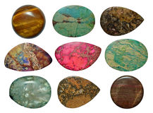 Uppsättning av olika färgrika stenar som isoleras på en vit Arkivbild