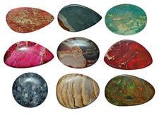 Uppsättning av olika färgrika stenar som isoleras på en vit Fotografering för Bildbyråer