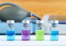 Uppsättning av olika medicinska små medicinflaskor för injektioner Ampuller med vätskefärger för blått för läkarbehandling rosa o Arkivbild