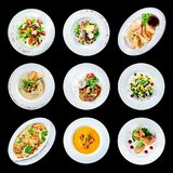 Uppsättning av olika plattor av mat som isoleras på svart bakgrund med Arkivbilder