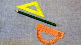 Uppsättning av plast- linjaler och en gradskiva mellan blyertspennan Arkivbild