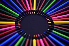 Uppsättning av realistiska färgrika kulöra blyertspennor på den svarta bakgrunden Arkivfoto