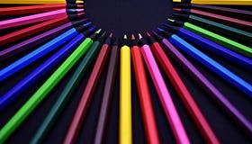 Uppsättning av realistiska färgrika kulöra blyertspennor på den svarta bakgrunden Fotografering för Bildbyråer