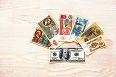 Uppsättning av rubelpengar för räkning USSR med 100 dollar på träbackgro Arkivbild
