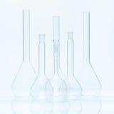 Uppsättning av sex tomma flatbottnade flaskor av olik kapacitet för mätningar Royaltyfri Foto