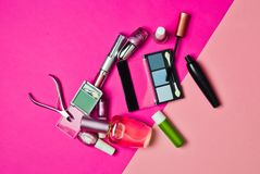 Uppsättning av skönhetsmedel för att applicera makeup på en rosa pastellfärgad bakgrund What& x27; s i women&en x27; kosmetisk på Royaltyfri Bild