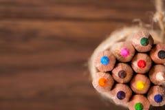 Uppsättning av skarpa färgrika blyertspennor som binds med ullrepställningen på ett trätomt bräde arkivbild