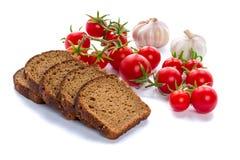 Uppsättning av skivor för svart bröd, körsbärsröda tomater och vitlök Arkivbilder