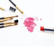 Uppsättning av sminkskönhetsmedlet, borste, rosa färgpulver, läppstift på vit bakgrund Royaltyfria Foton