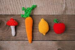 Uppsättning av stack leksaker citron, morot, äpple, amanita på träbakgrund Tidigare känsel- utveckling av barn, hantverkleksaker arkivfoton