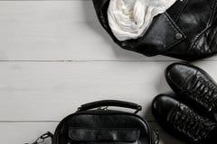 Uppsättning av stilfulla kläder för svart kvinna` s, tillbehör för mode för kvinna` s, svart stil, på vit träbakgrund Lekmanna- l royaltyfri fotografi