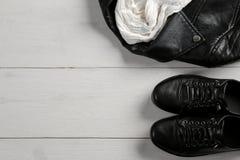 Uppsättning av stilfulla kläder för svart kvinna` s, tillbehör för mode för kvinna` s, svart stil, på vit träbakgrund Lekmanna- l royaltyfria bilder