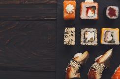 Uppsättning av sushi på svart wood bakgrund, bästa sikt Arkivbild