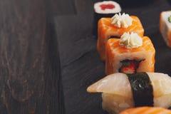 Uppsättning av sushi på svart wood bakgrund, pov Royaltyfri Fotografi