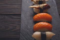 Uppsättning av sushi på svart wood bakgrund, pov Royaltyfri Bild