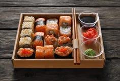 Uppsättning av sushimaki och rullar på svart lantligt trä Royaltyfri Foto