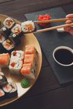 Uppsättning av sushimaki och rullar på svart lantligt trä arkivbild
