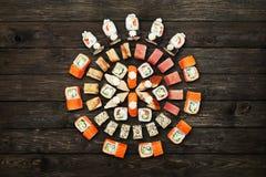 Uppsättning av sushimaki och rullar på svart lantligt trä Arkivfoto