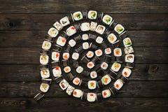 Uppsättning av sushimaki och rullar på svart lantligt trä Arkivfoton