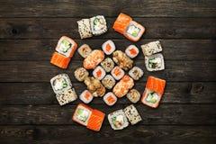 Uppsättning av sushimaki och rullar på svart lantligt trä Fotografering för Bildbyråer