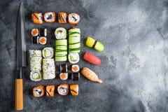 Uppsättning av sushirullar och kniven på mörk bakgrund traditionell matjapan kopiera avstånd Lekmanna- lägenhet Top beskådar Royaltyfri Foto