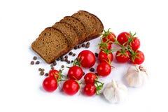 Uppsättning av svart bröd, körsbärsröda tomater och vitlök Arkivbild