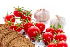 Uppsättning av svart bröd, tomater och vitlök Arkivfoto