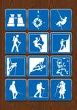 Uppsättning av symboler av utomhus- aktiviteter: kikare kompass och att fotvandra och att klättra Symboler i blåttfärg på träbakg Arkivfoto
