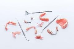 Uppsättning av tandproteser och tand- hjälpmedel på vit bakgrund Royaltyfri Fotografi