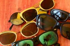 Uppsättning av tappningsolglasögon på brun träbakgrund Royaltyfri Foto