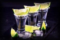 Uppsättning av tequilaskott på en mörk bakgrund Arkivbild