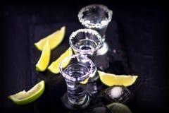 Uppsättning av tequilaskott på en mörk träbakgrund Fotografering för Bildbyråer