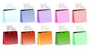 Uppsättning av tio realistiska pappers- påsar i stora partier för mångfärgad lutning för att shoppa med pennor i form av en inskr Arkivfoton