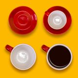 Uppsättning av tomma och fulla röda koppar och tefat Kaffeuppsättning på en gul bakgrund Fotografering för Bildbyråer