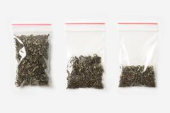 Uppsättning av TOMMA tre, HALVA OCH FULLA plast- genomskinliga blixtlåspåse med torrt grönt te som isoleras på vit Vakuumpackemod Royaltyfri Foto