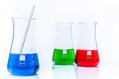 Uppsättning av tre resistenta flaskor för konisk temperatur med färgflytande Arkivfoton