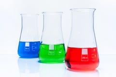 Uppsättning av tre resistenta flaskor för konisk temperatur med färgflytande Arkivfoto