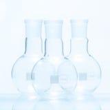 Uppsättning av tre tomma sfäriska plana bottnade resistenta flaskor för temperatur Arkivfoto