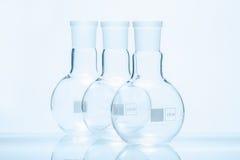 Uppsättning av tre tomma sfäriska plana bottnade resistenta flaskor för temperatur Royaltyfria Foton