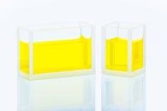 Uppsättning av två cuvettes med gul flytande Arkivbilder