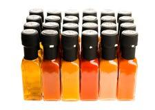 Uppsättning av varma Chili Sauce glasflaskor på vit bakgrund Arkivbild