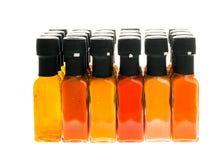 Uppsättning av varma Chili Sauce glasflaskor på vit bakgrund Royaltyfria Foton