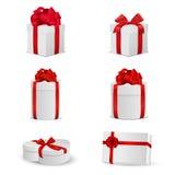 Uppsättning av vita gåvaaskar med röda pilbågar och band Arkivbild